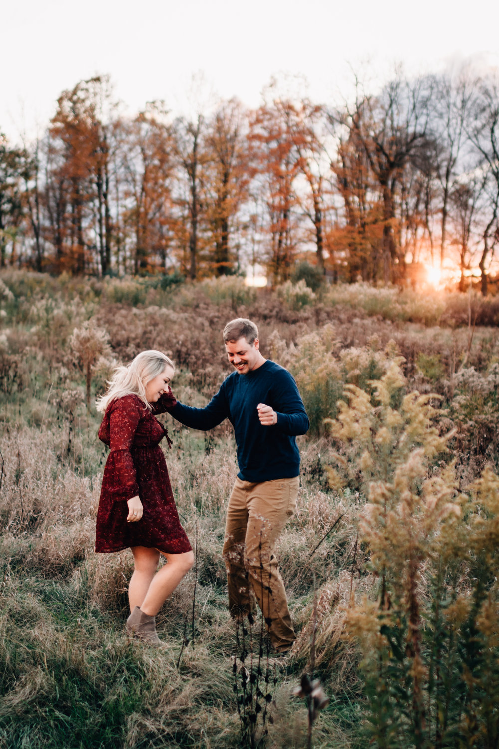 Engaged couple dancing in field at sunset