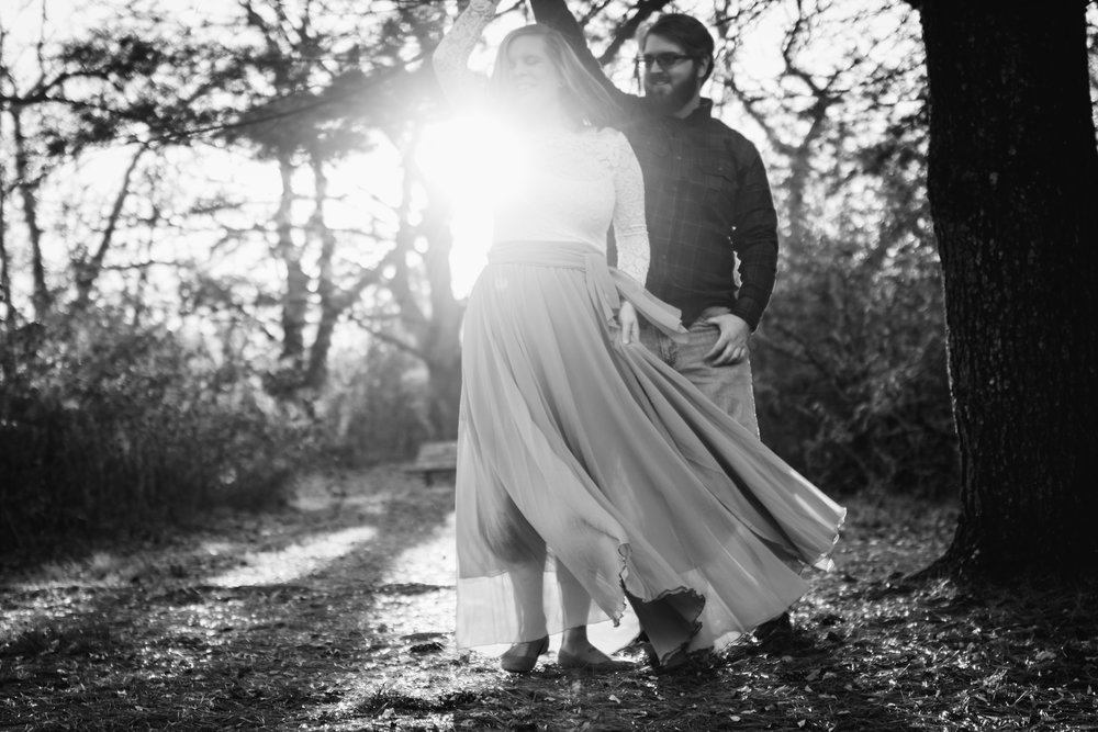 Epic sun shining through as guy twirls girl in skirt around