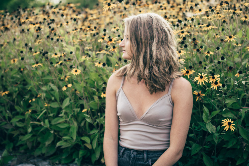 Girl sitting by yellow flowers
