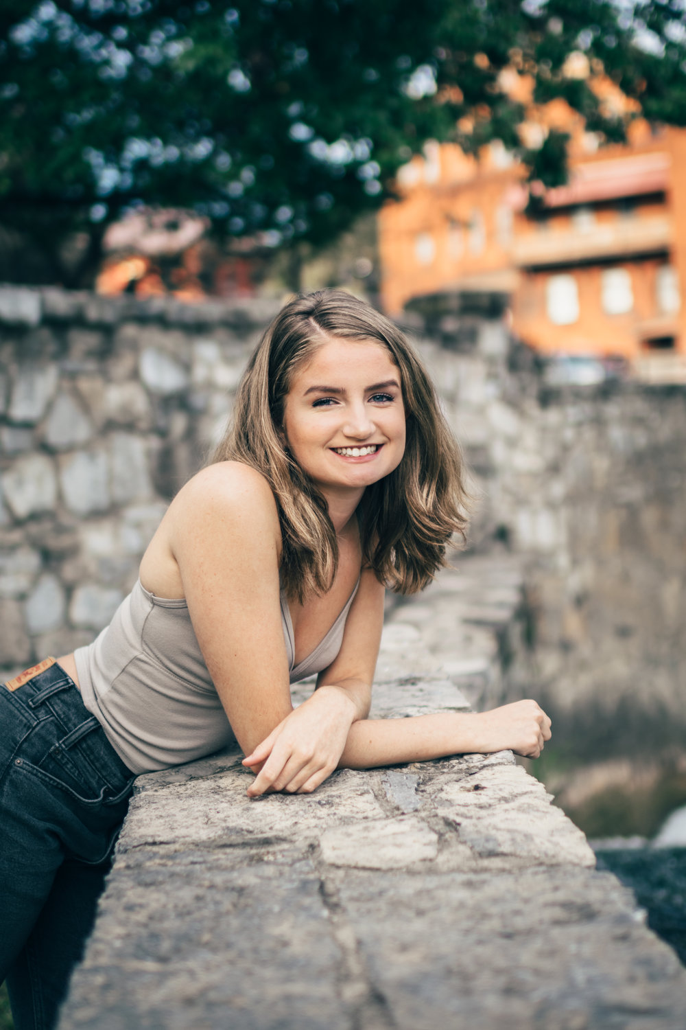 Smiling girl leaning on stone