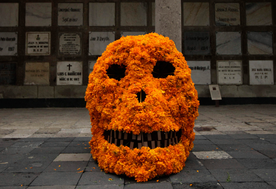 a-skull-covered-in-marigolds-rests-in-front-of-a-wall-of-graves-mexico-city-oct-27-2009-photographed-for-ap-photo-by-gregory-bull-via-bigpicture.jpg