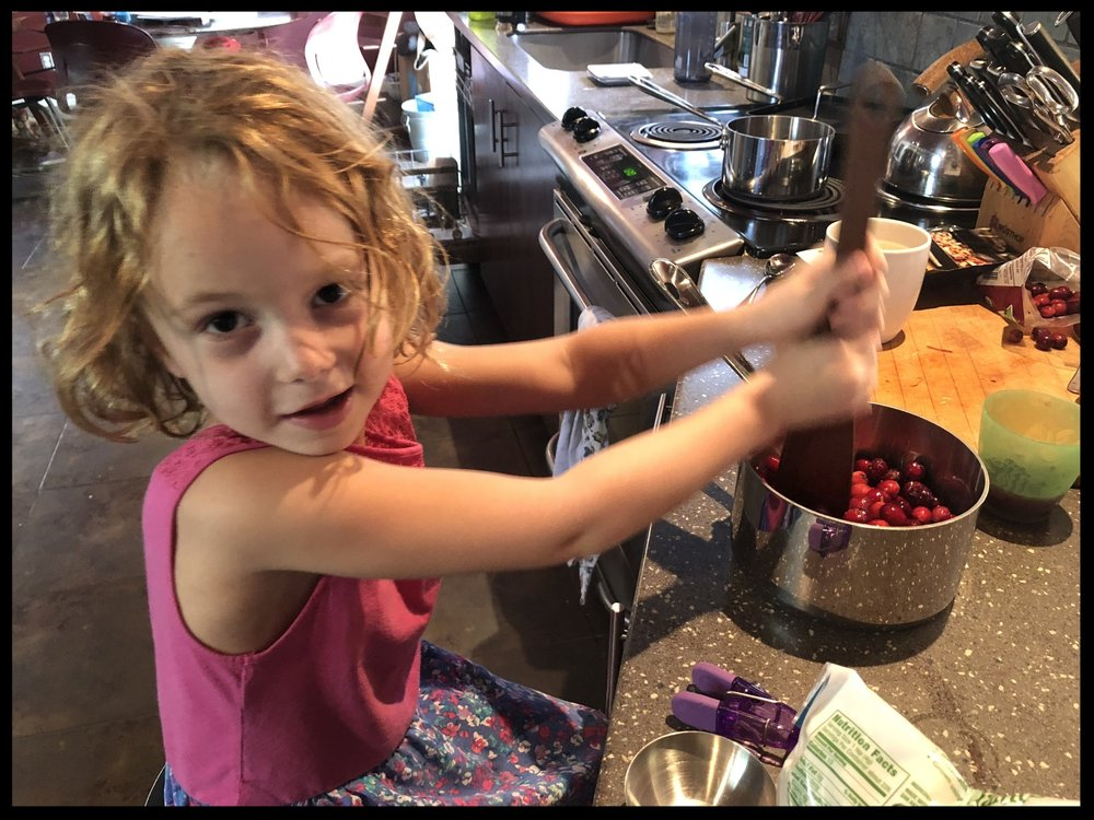 "My youngest ""hard at work"" on the cranberry sauce last year. This is a super easy recipe. The ""hardest"" part is deseeding the pomegranate. Fun job for kids."