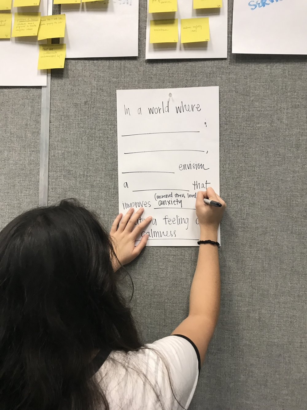 My teammate writing out what we came up with during a design friction exercise.