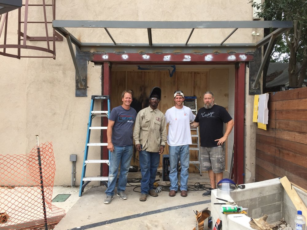 Last big construction obstacle was the front door and awning. The studio was constructed by Fred Willams Construction.  [left to right] Bobby Layne (lead carpenter), John Reginald (welder), Aaron Somers (apprentice carpenter), Matt Dunnam (lead carpenter) (May 2017)