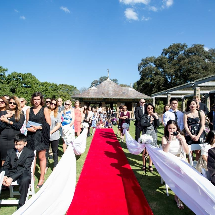 red_carpet_aisle_runner_sydney_royal_botanical_gardens_outddor_weddingsRBG - Rose Garden - Ceremony - Red carpet, white folding chairs and medium black flower stand with connected organza and silk flowers.jpg