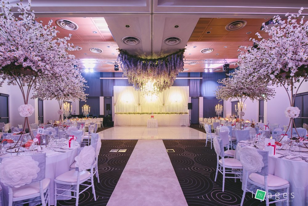 Waterview - Lake Room - 3 Window white backdrop with 12 arm sofia chandeliers, white silk cherry blossom trees, purple wisteria hanging above dance floor with Sofia 18 arm chandelier in the middle and fiori chair caps.jpg