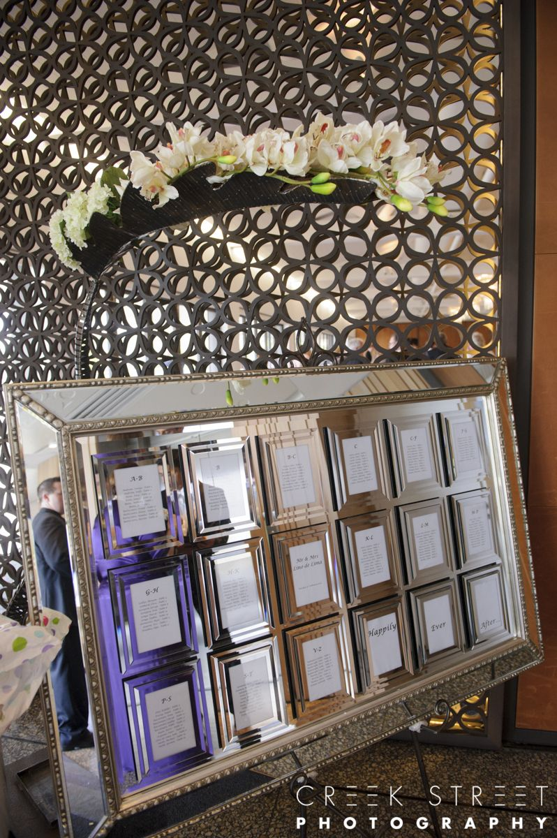 18 mirrored frame guest seating plan with black wrought iron easel and an exotic leaf.jpg