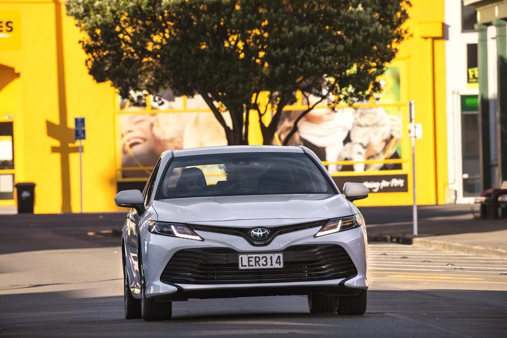 2018 Toyota Camry, GX hybrid, Glacier White, front shot.jpg