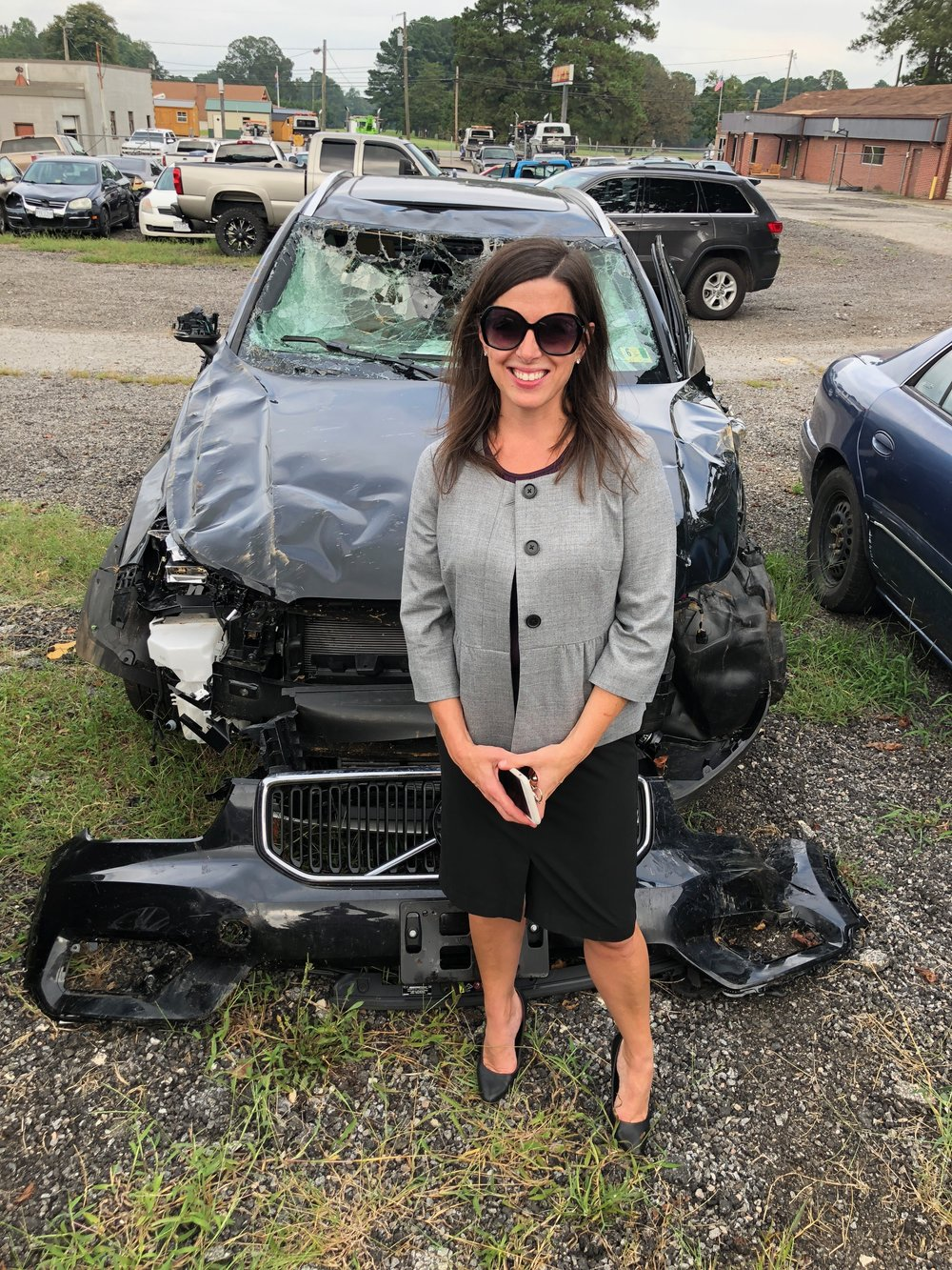 the badass survivor in front of the car that sacrificed itself to save her life