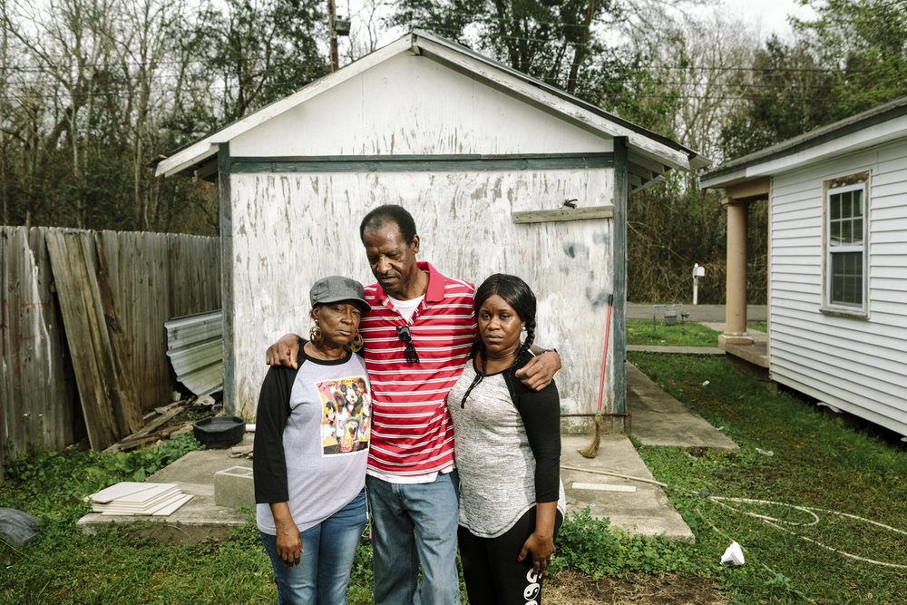Reserve, LA - Feb 20, 2017 - David Sanders (59) stands with his wife Laverne Sanders (59, L) and daughter Shannon Perrilloux (35) in the back yard of their home on East 31st Street, which borders the fence line of the Dupont/Denka plant.