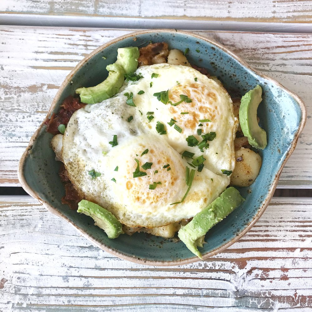 Skillet Hash-Farmhouse (Two cage-free eggs any style atop fresh, seasoned potatoes, bacon, avocado, house-roasted onions and tomatoes, Cheddar and Monterey Jack. Served with whole grain artisan toast.)