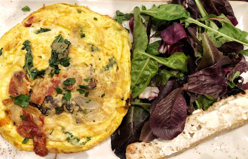 Frittata Rustica:A classic Italian-style omelet with kale, house-roasted Crimini mushrooms, onions and tomatoes topped with Mozzarella and Parmesan cheese. Served with ciabatta toast.