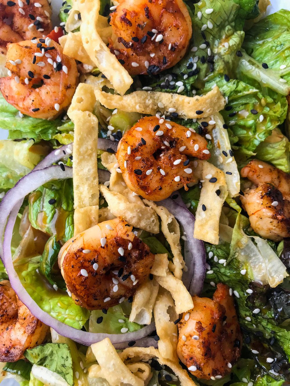 Asian Shrimp Salad from California Fish Grill - Succulent shrimp on a bed of mixed greens topped with sesame seeds, tomatoes, almonds, crispy wontons, red & green onions, and topped with our tangy Asian dressing.$9.99