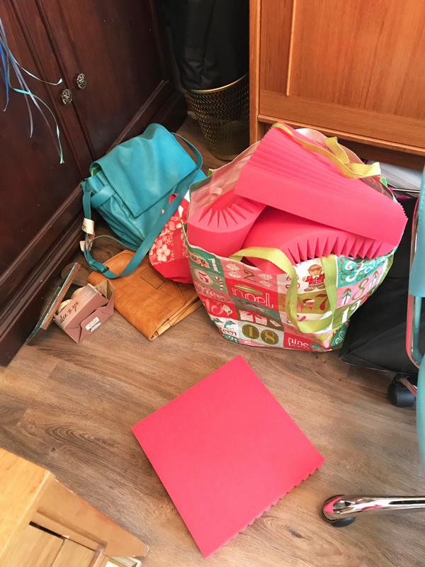 Those red foam pieces are for soundproofing the room when I record my videos. The lights for filming are to the right of that big shopping bag. Normally those items are stored in the garage closet.