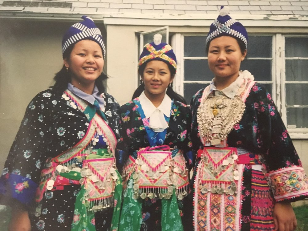 Hnub (right) and her sisters wearing traditional clothing for the Hmong New Year. Hers features the hand-stitched fabric she'd created as a child, along with silver jewelry, saved for New Year celebrations.