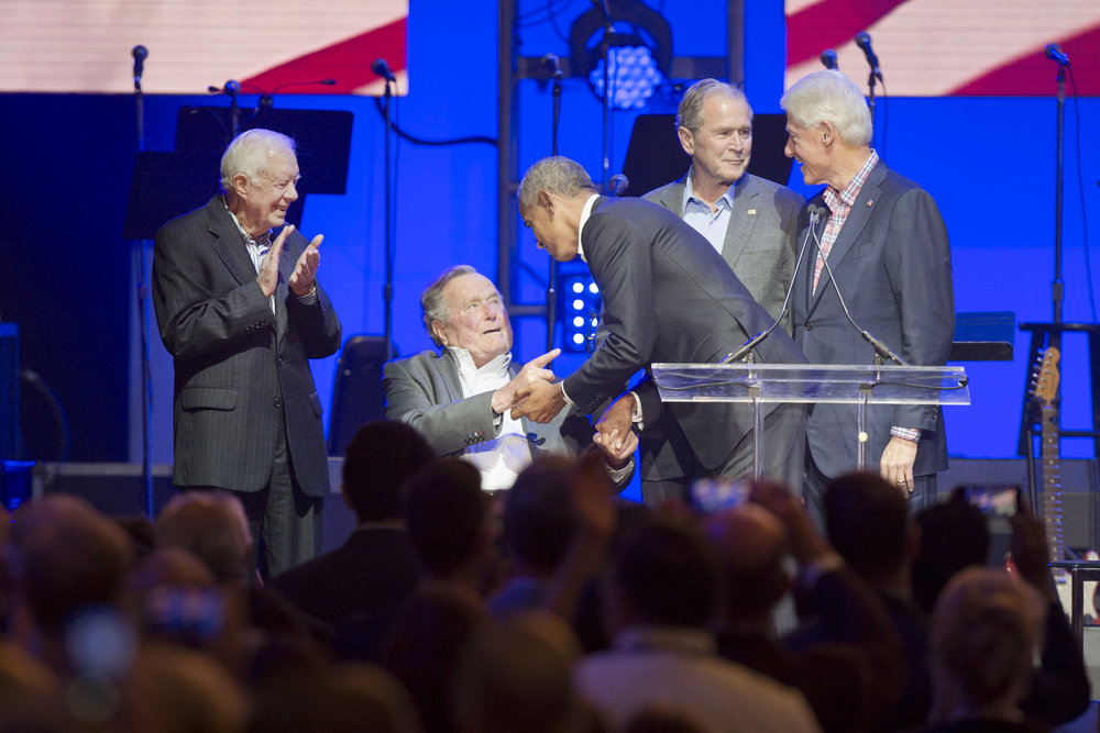 "Former President Barack Obama shakes former President George H.W. Bush's hand while sharing the stage with former Presidents Jimmy Carter, George W. Bush and Bill Clinton at the ""One America Appeal"" hurricane relief concert on Saturday, Oct. 21, 2017, at Reed Arena in College Station, Texas. (Laura McKenzie/The Eagle)"