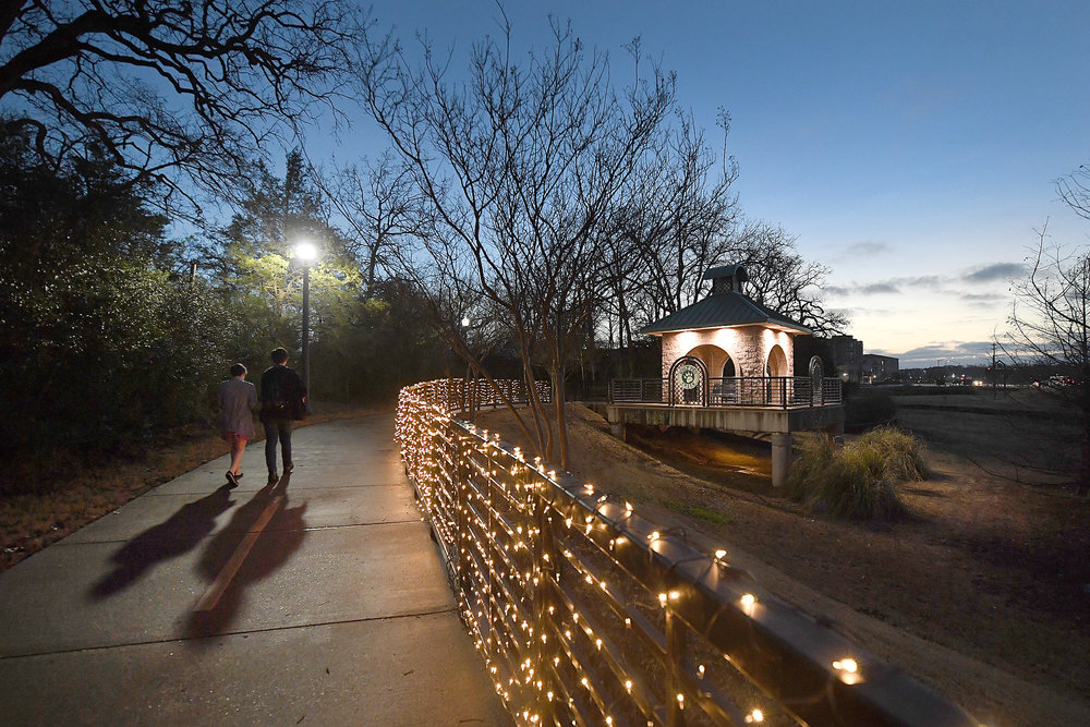 Dalanie Ward and Joseph Wise walk the Trail of Lights at Wolf Pen Creek Park in College Station, Texas, during a Wednesday, Feb. 14, 2018 date night event that included food trucks, live music and horse-drawn carriage rides. (Laura McKenzie/The Eagle)
