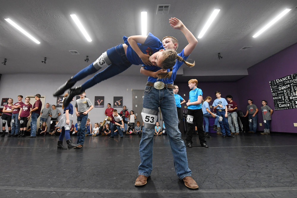 Grayson Coker, 13, swings his partner Allie Fleener, 11, in the air during the Lil' Wranglers audition at Expressions Dance and Music on Saturday, July 21, 2018, in College Station, Texas. (Laura McKenzie/The Eagle)