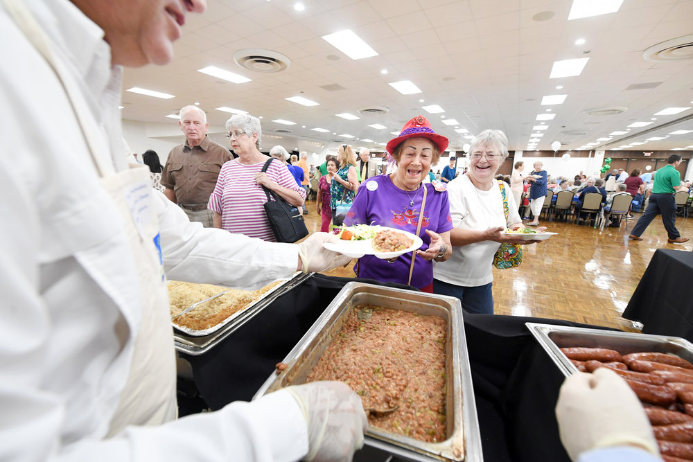 Lenora Patranella, center, and Micki Miskimen make their way through the food line at the Brazos Center on Wednesday, Aug. 8, 2018, during the annual Feast of Caring, a fundraiser for the Brazos Valley Food Bank. Plates of rice, beans, sausage, salad, bread and dessert were served during the lunchtime event, which also raised awareness of food insecurity in the Brazos Valley. (Laura McKenzie/The Eagle)