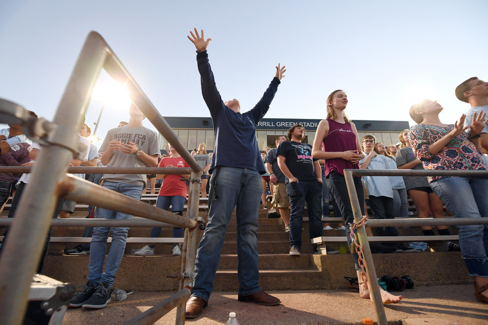 "Joshua Jordan, 17, center, raises his hands as students from area schools and other members of the community sing a praise song Wednesday, Oct. 3, 2018, during the Fellowship of Christian Athletes event ""Fields of Faith"" at Merrill Green Stadium in Bryan, Texas. Hundreds gathered for the student-led event to celebrate and share their faith. Similar events have been held or are scheduled at athletic fields across the country. (Laura McKenzie/The Eagle)"