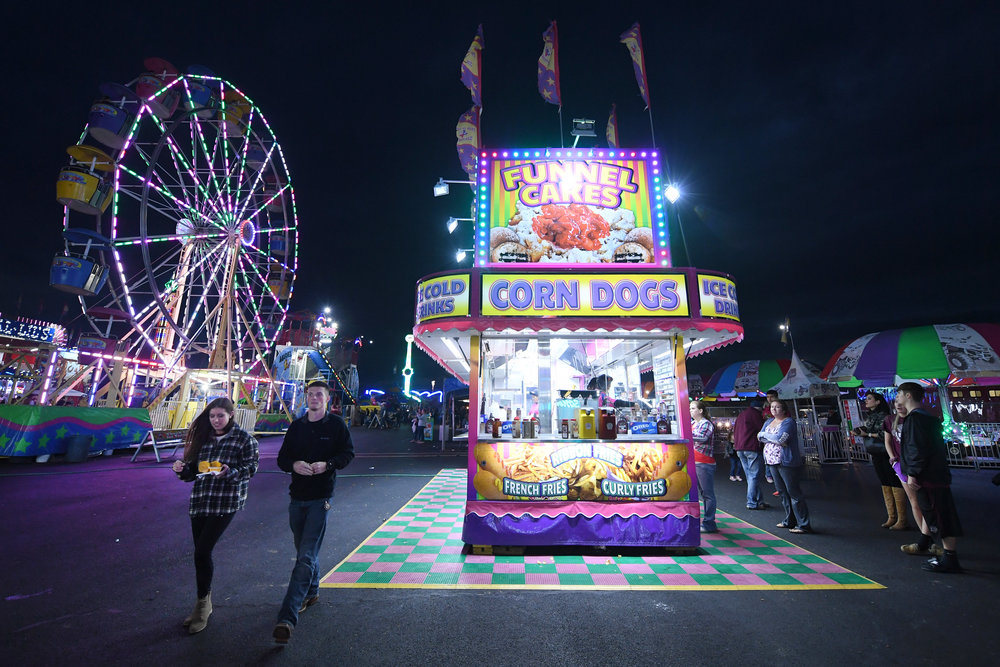 Abby Merriman, left, her husband Max Merriman and others stop at a food vendor for carnival snacks during the Brazos Valley Fair and Rodeo on Saturday, Oct. 20, 2018, in Bryan, Texas. (Laura McKenzie/The Eagle)