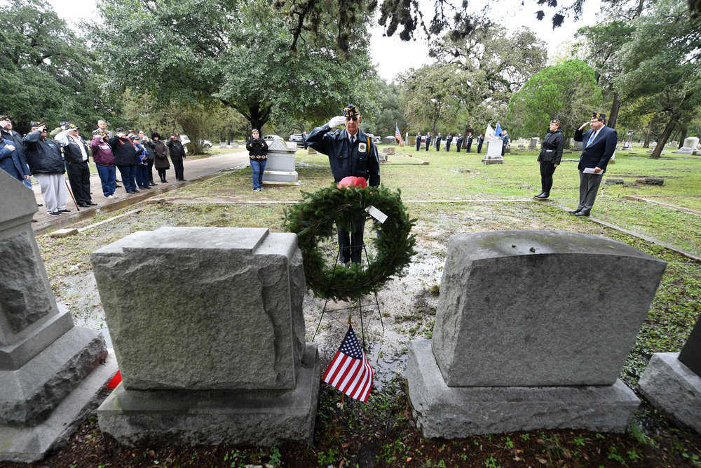 Legionnaire David Marion, center, salutes after placing a wreath beside the grave of Cyrus Earle Graham during a ceremony observing the 100th anniversary of his death on Friday, Nov. 9, 2018, at the Bryan City Cemetery in Bryan, Texas. When American Legion Post 159 was formed after World War I, charter members voted to name the post in honor of Graham, who was killed in a plane crash in France on Nov. 9, 1918 at the age of 24. (Laura McKenzie/The Eagle)