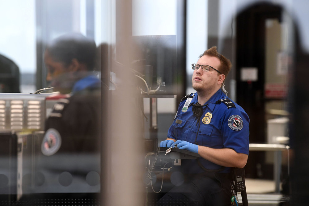"Transportation Security Officer Shawn Rasmussen screens passenger baggage while working Friday, Jan. 11, 2019, at the security checkpoint at Easterwood Airport in College Station, Texas. Officers are considered ""essential"" staff and were required to work during the government shutdown. (Laura McKenzie/The Eagle)"