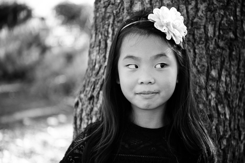 Little girl with bow in her hair in front of a cedar tree in Cedar Grove Park in Tustin, California. Full post at lisahuchen.com.