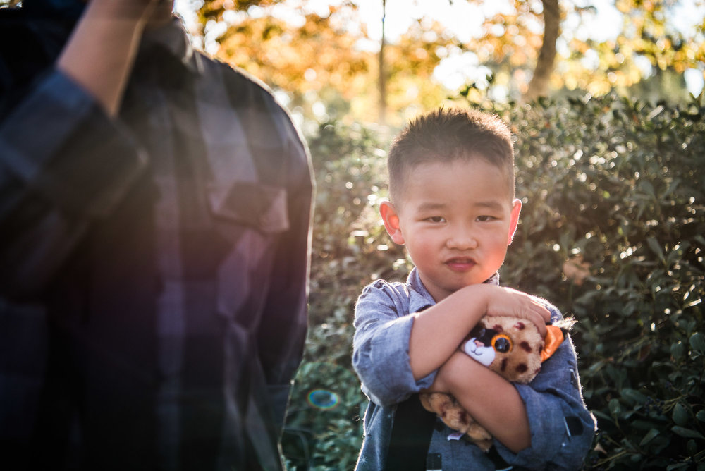Little boy hugging a stuffed animal tiger in a family portrait session in Cedar Grove Park in Tustin, California. Full post at lisahuchen.com.