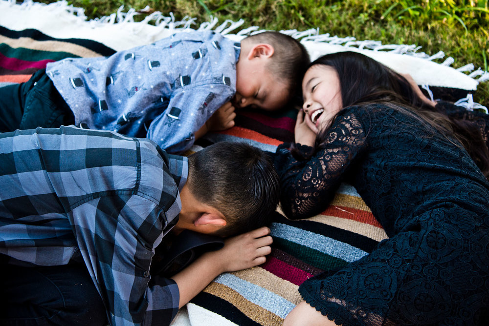Kids lying on a Native American motif blanket in family portrait session in Cedar Grove Park in Tustin, California. Full post at lisahuchen.com.