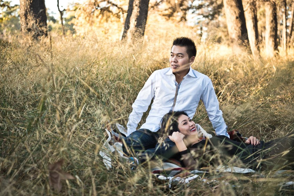 Asian couple:  mom lying on dad's lap in the grassy field at Cedar Grove Park in Tustin, California.