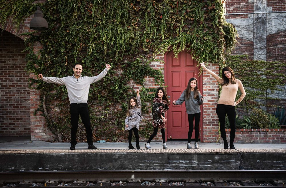 Lisa Hu Chen orange county family photographer family of five dancing at the train station in san juan capistrano
