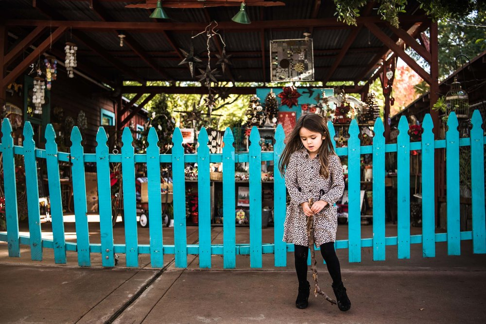 Lisa Hu Chen orange county family photographer little girl in front of a blue picket fence in san juan capistrano