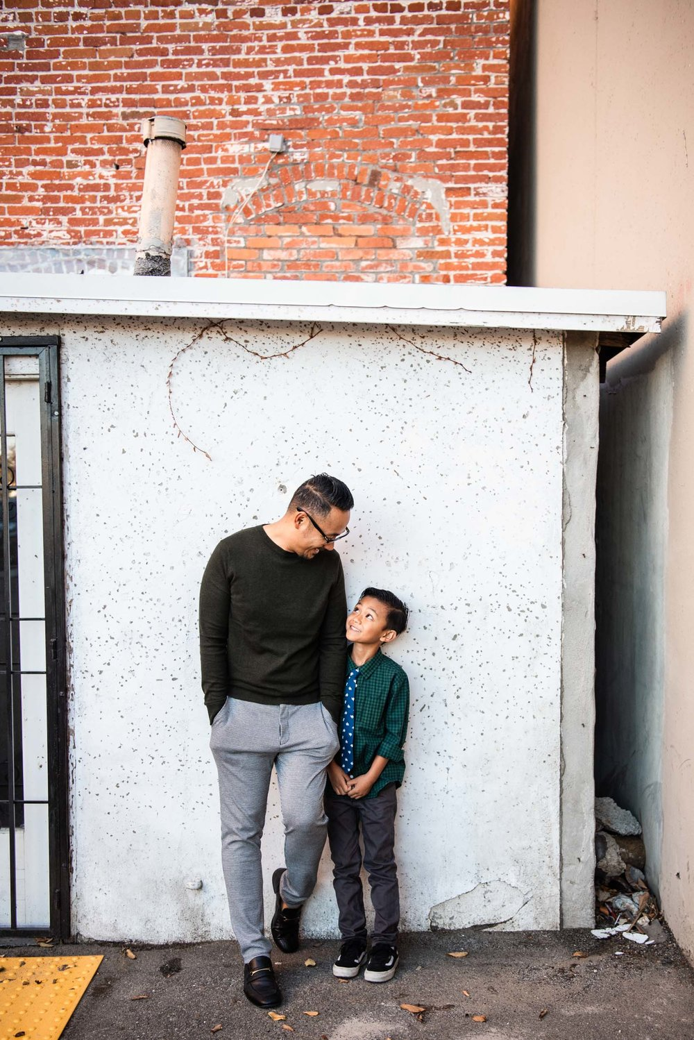 Lisa Hu Chen orange county family photographer | father and son looking at each other leaning against a building in Old Town Orange