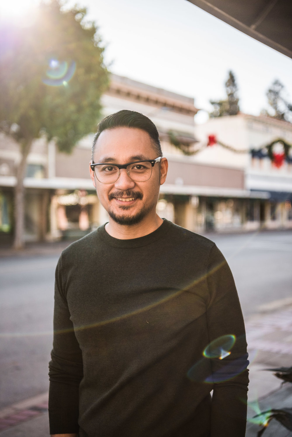 Lisa Hu Chen | man in glasses bathed in sunlight smiles while standing in the middle of the street in Old Town Orange