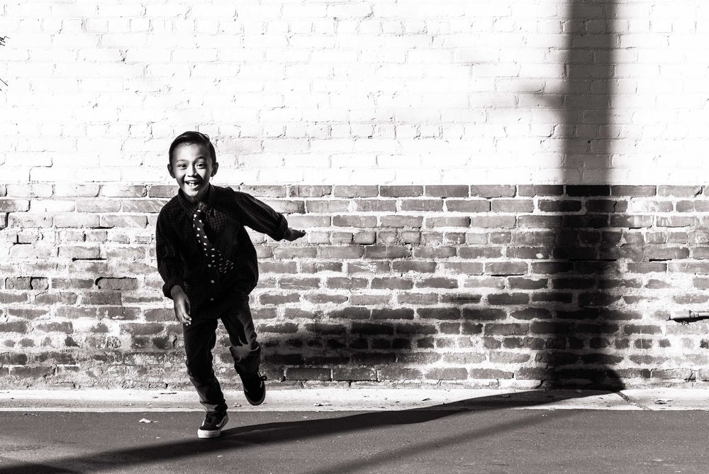 Lisa Hu Chen | young boy smiling and running in front of a brick wall in Old Town Orange