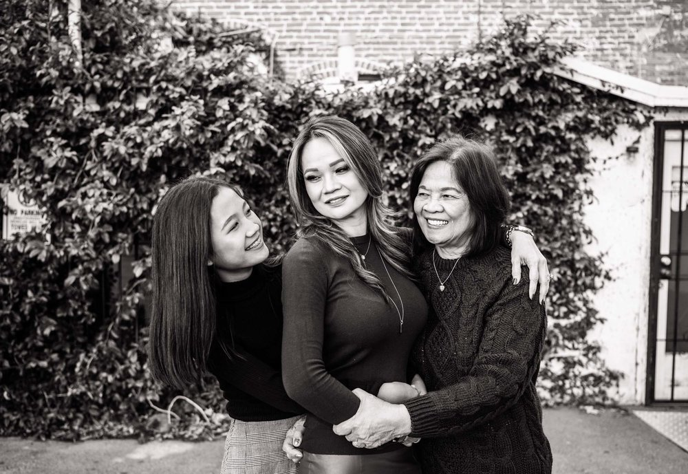 Lisa Hu Chen | three generations of grandma, mom and young girl hugging and smiling in front of an ivy wall in Old Town Orange