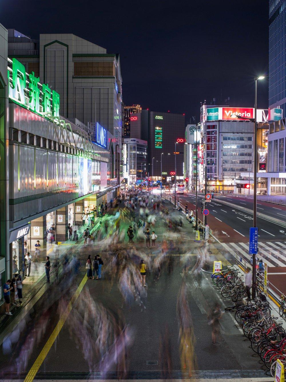 Framför JR Shinjuku Station, världens största tågstation, en vanlig sensommarkväll