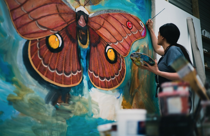 Chelsea Hopkins-Allan in her studio painting a larger than life sized Helena Gum Moth   Taken by Luke Griffiths @ManWithRockProductions  www.manwithrock.com