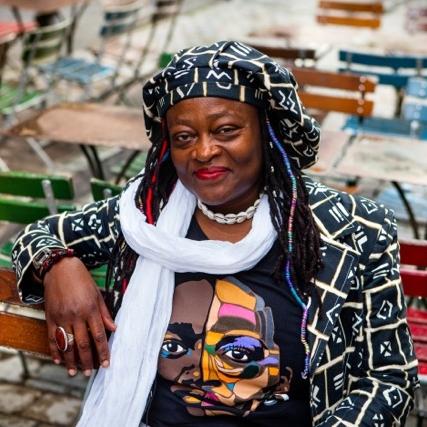 """Marthe Djilo Kamga Marthe Djilo Kamga is de oprichter en huidige coördinator van het Massidami festival. Zij heeft zich zowel persoonlijk als beroepsmatig altijd gericht op vraagstukken over kwetsbaarheid, identiteit en gelijke kansen. Haar passie voor kunstzinnige en culturele projecten (film, theater, fotografie, enz.) is haar drijfveer om afbeeldingen en publieke ruimtes opnieuw te claimen voor personen in 'onzichtbare' posities. Terugkerende thema's in haar werk zijn het gelijktijdig kunnen bestaan van verschillende identiteiten en de diversiteit van kunstzinnige en culturele expressie. Ze doet een beetje van alles en vraagt zich af of één leven wel genoeg tijd biedt om al haar interesses na te jagen. Marthe beschouwt zichzelf net zo min een strijder als een onderzoeker (in verband met haar werk: """"Wanneer vrouwen van andere vrouwen houden: een beschouwing van vrouwelijke homoseksualiteit in Kameroen."""") Doordat ze heeft kunnen profiteren van academisch onderwijs is zij naar eigen zeggen een 'belemmerd kunstenaar in zelfanalyse'."""