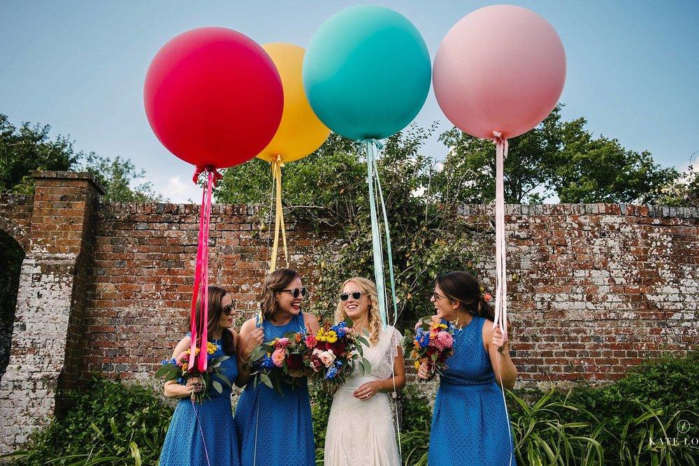 bruden och hennes tärnor samt färgglada jätteballonger på engelskt bröllop i Surrey