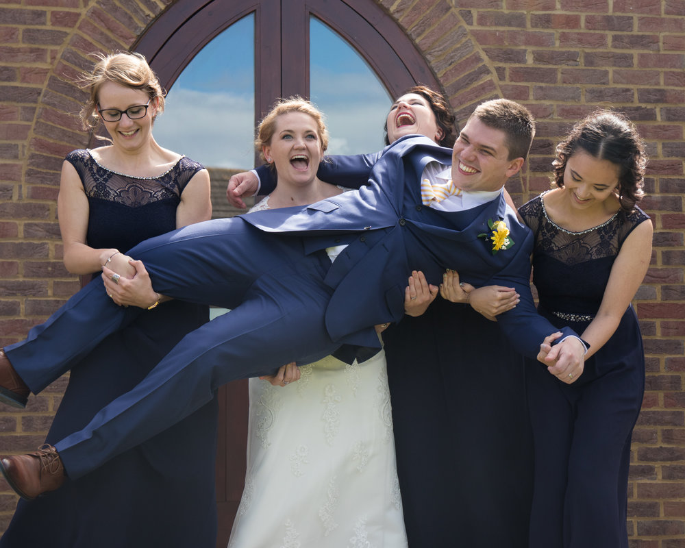 Bride and bridesmaids holding up the groom at a wedding in St Thomas's Church  Luton Bedfordshire