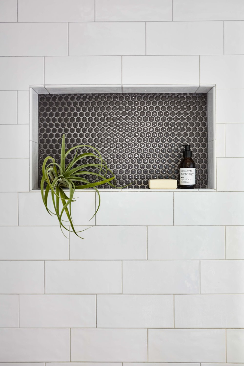 Shower niche with large subway tile and penny tile.