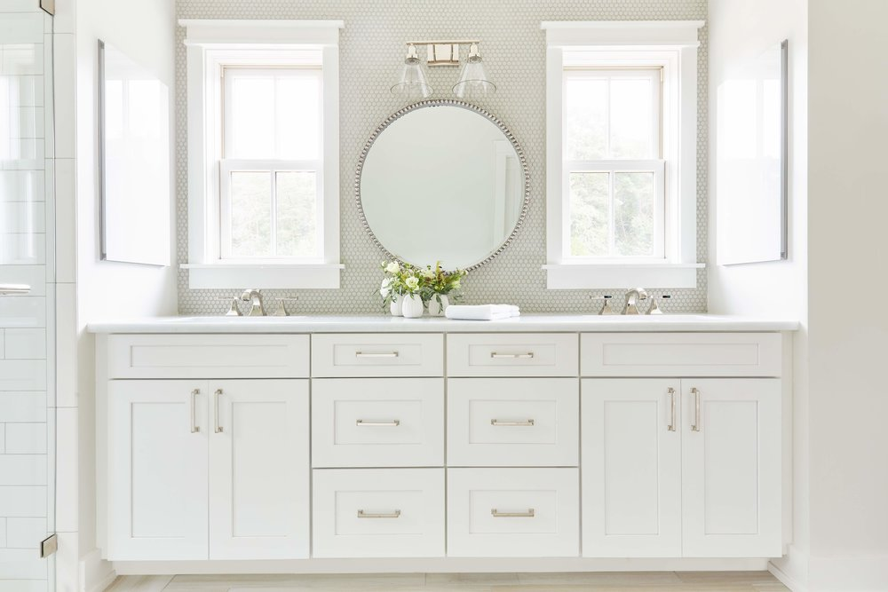 Side medicine cabinets conceal mirrors while windows over the sink provide light and views.