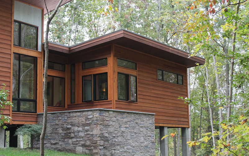 Exterior combines textures including wood, corrugated metal and natural stone.