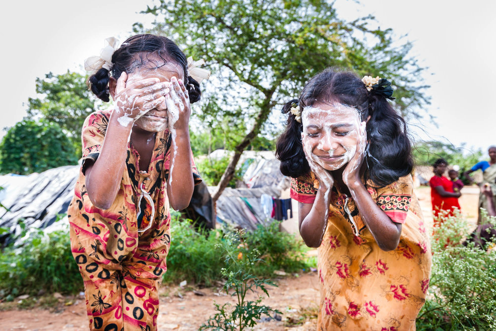 Two Dalit girls living in a slum area of Bengaluru wash their faces before going to school. Non of the families in the girls' community had a private bathroom and washed instead on wasteland. Assisted by the local Dalit community, the picture was taken for Being Untouchable, an exhibition of intimate portraits illustrating the injustice, poverty and inequality suffered by many of India's 167 million Dalits. Photo © Marcus Perkins.