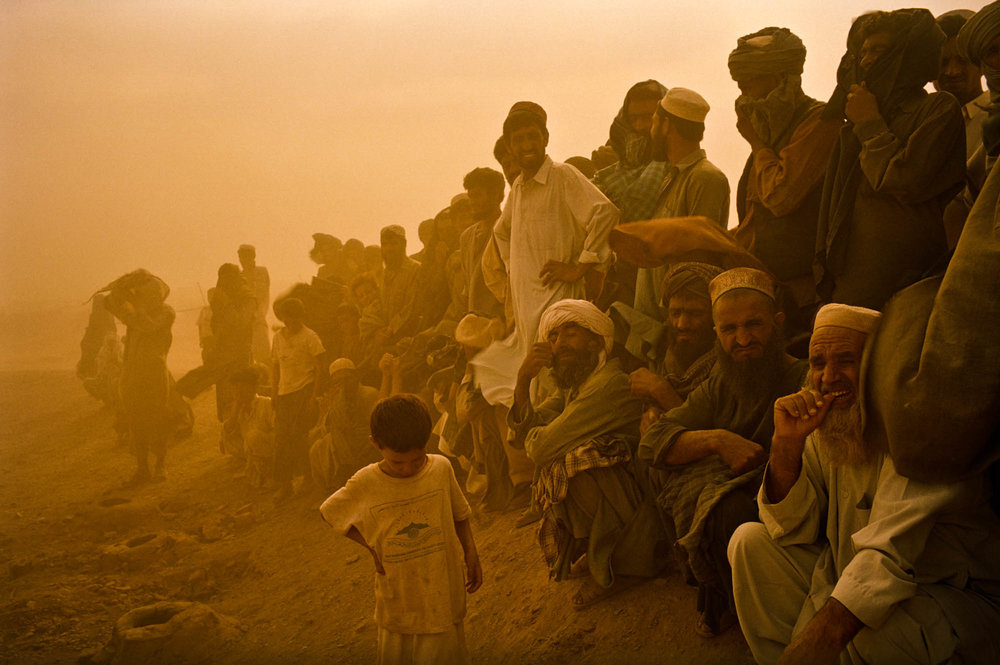 Blighted by war and famine, Afghan men with no jobs and no homes gather on the fringes of a refugee camp during a dust storm. Tribal territories in northern Pakistan. Photo © Marcus Perkins.