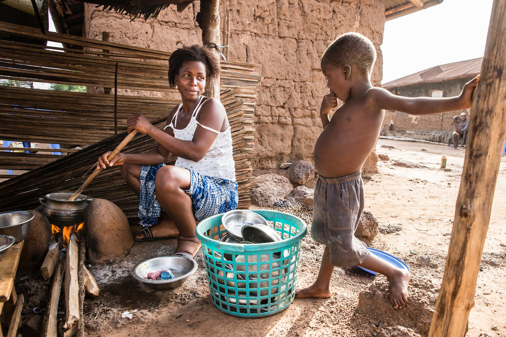 A scene replicated around the world - Silvi Degbe's son hangs around the family kitchen waiting for his dinner. Silvi, who has lived with LF since 1993, works as a corn saleswoman. Tsave, southern Togo. Photograph: Ecce Opus / © Copyright GSK