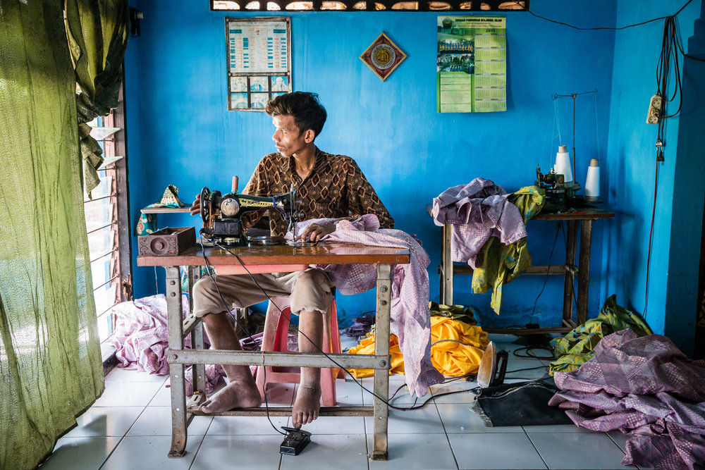Miftahudin owns a small but successful tailoring business which he runs from home. The effects of lymphatic filariasis are not life-threatening. However, it is important for those with this condition to find work and a lifestyle that lowers the risk of damaging affected limbs. Pekalongan City, Indonesia. Photograph: Ecce Opus / © Copyright GSK