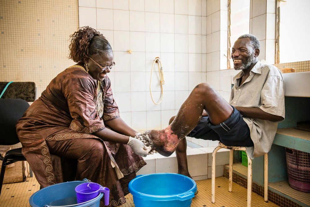 Adama Zoundi finds the spirit to share a joke with Mme Kabre (Ministry of Health, Burkina Faso) whilst she washes his infected foot. Adama is part of a newly established group of LF patients who meet regularly to share their experiences and to support each other. Ouagadougou, Burkina Faso. Photograph: Ecce Opus / © Copyright GSK